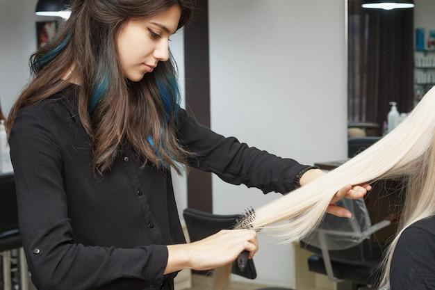 Парикмахер расчесывает волосы клиента в модном стиле. модная женщина.