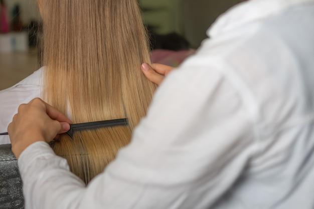 美容院で美容院でクライアントの長い髪をとかす