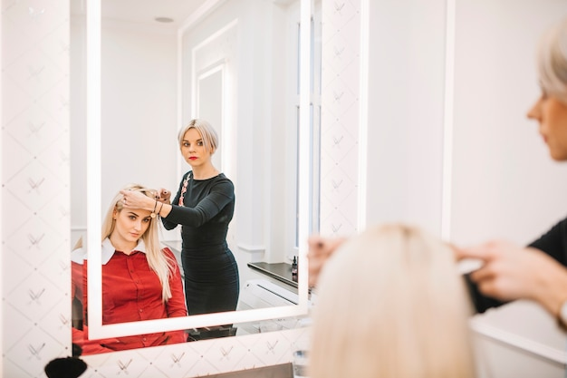Hairdresser consulting client in salon