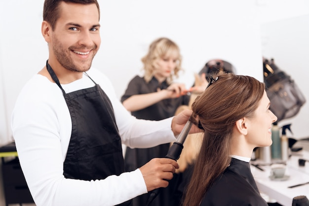 Hairdresser curling brown hair of beautiful woman.