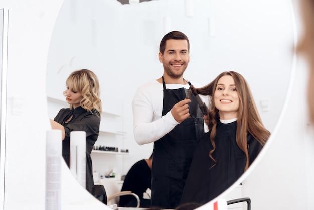 아름 다운 여자의 검은 갈색 머리를 컬링하는 미용사.