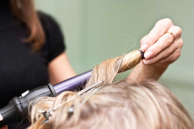 Hairdresser curling hair in a beauty salon