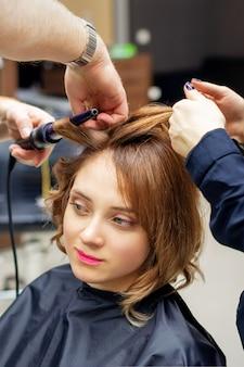 Парикмахер завивает длинные русые волосы