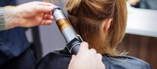 長い薄茶色の髪をカールする美容師