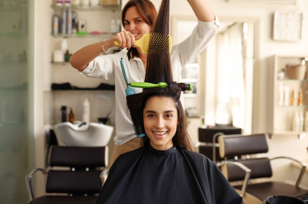 Hairdresser curls and combs woman's hair, hairdressing salon. stylist and client in hairsalon. beauty business, professional service