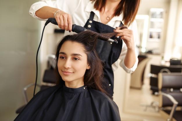 미용사는 여자의 머리카락, 미용실을 컬합니다. 헤어 살롱의 스타일리스트와 클라이언트. 뷰티 사업, 전문 서비스