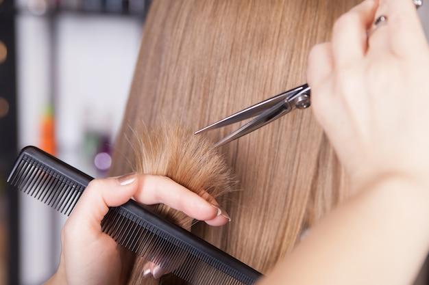 美容師は女性のブロンドの髪をカットしました。閉じる。