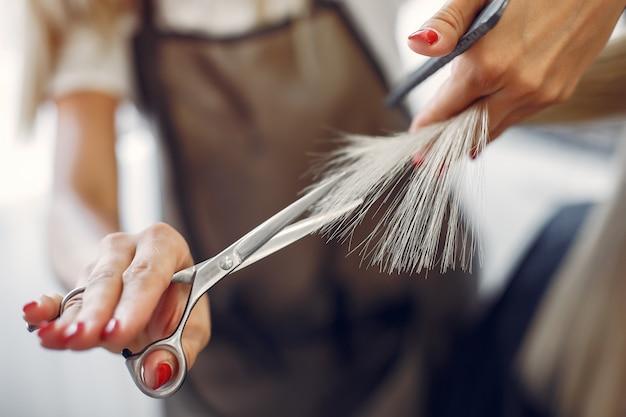 Парикмахер стрижет волосы своего клиента в парикмахерской