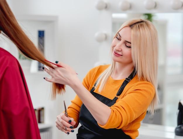 美容院でハサミを使ってクライアントの髪をカットした美容師。金髪の女性スタイリストが散髪する