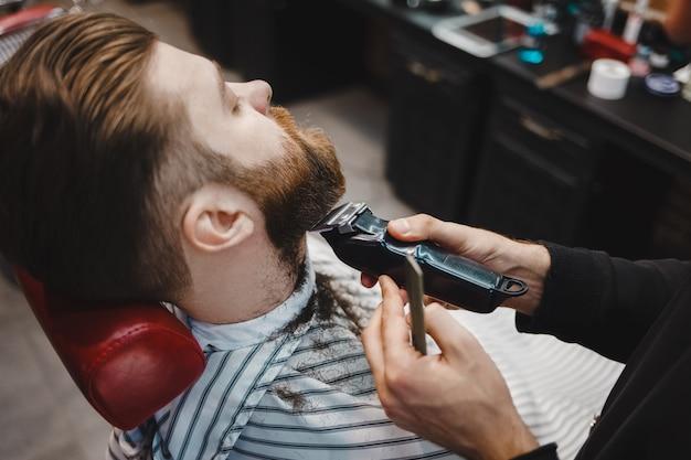 Hairdresser cuts a beard