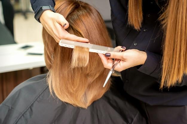 Парикмахер подстригает каштановые волосы молодой женщине в салоне красоты
