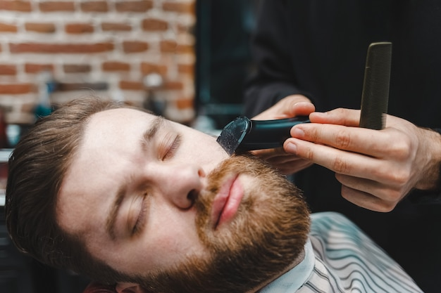 Hairdresser cuts client's beard with electric trimmer