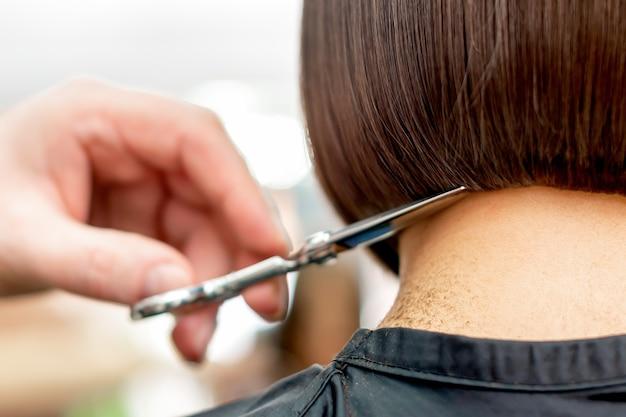 Парикмахер стрижет кончики волос крупным планом