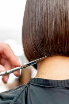 Парикмахер подстригает кончики волос короткой прически женщины сзади с копией пространства тонированное