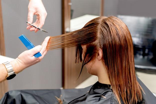 Hairdresser cuts hair of woman