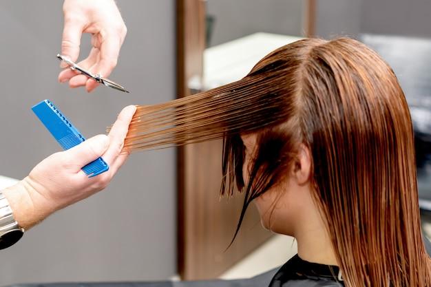 Hairdresser cuts hair of woman.