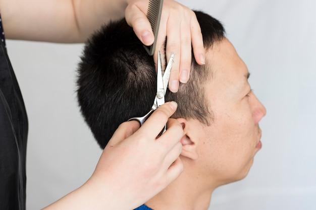 Hairdresser cuts a man