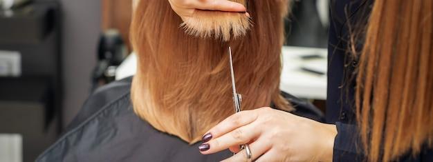 Парикмахер стрижет рыжие волосы кончиками