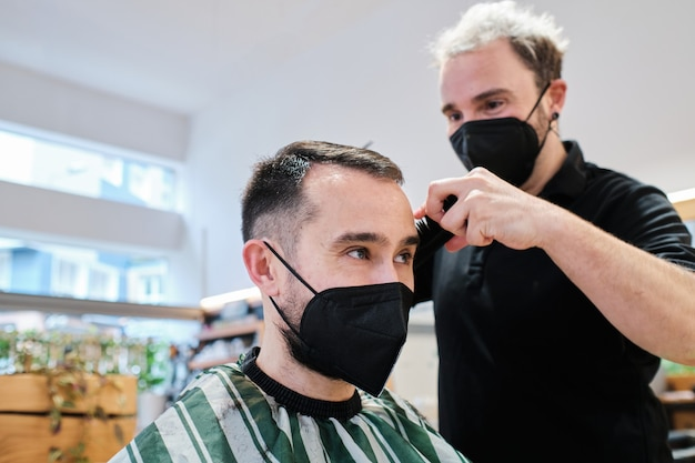 보호 마스크로 고객의 머리를 자르는 미용사