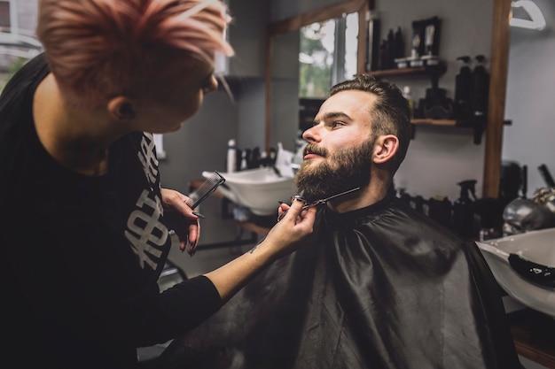 Hairdresser cutting beard of client