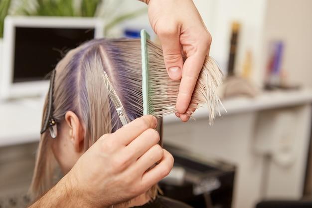 Парикмахер стрижет светлые волосы женщины в салоне красоты