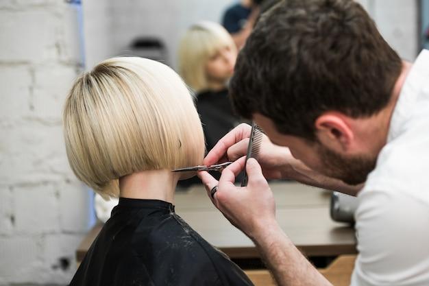 電気かみそりのクローズアップとサロンで美容師がクライアントの髪をカットします。