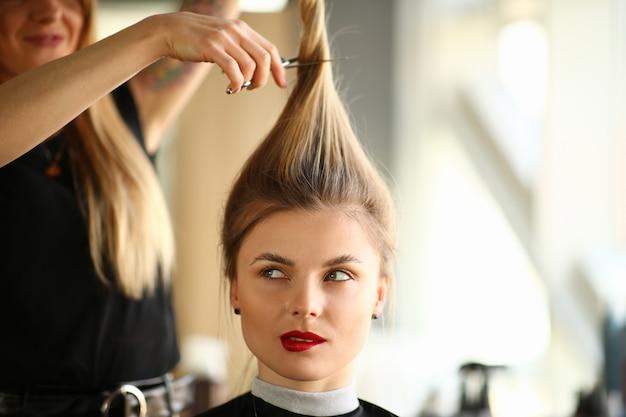 金髪の女性の肖像画に髪を切る美容師