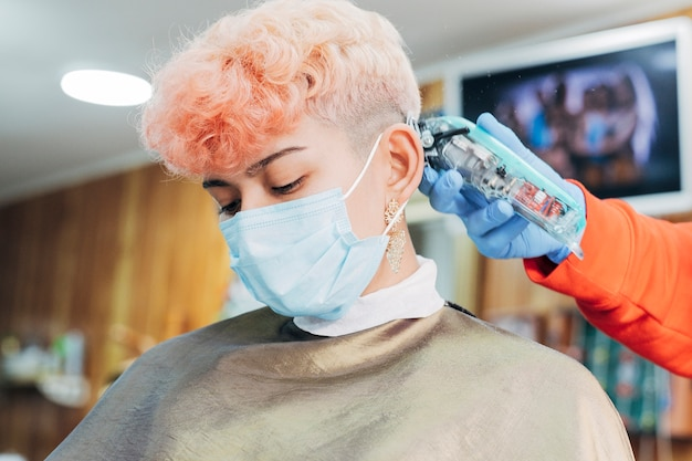 美容師は、理髪店でフェイスマスクを着ている女性に髪をカットします。 covidの後の新しい正常。