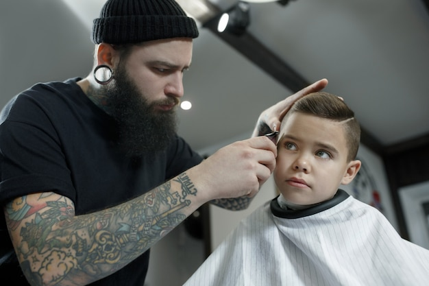 Hairdresser cutting little boy's hair