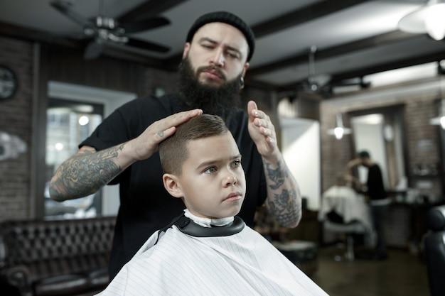 Parrucchiere che taglia i capelli del ragazzino