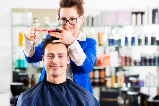 Hairdresser cutting man hair in barbershop