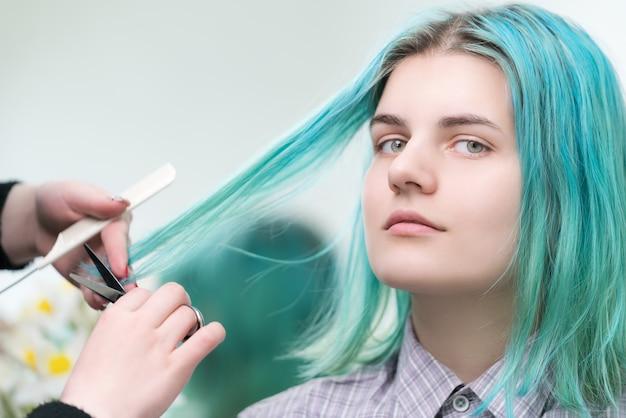 若い女性の長い緑髪をはさみで切る美容師。プロの美容院でのヘアケア。