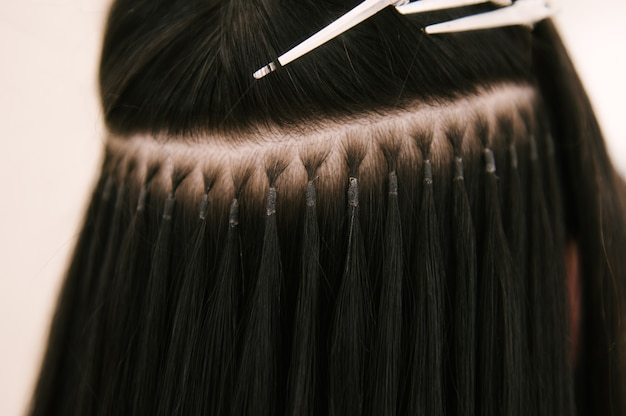 The hairdresser does hair extensions to a young girl in a beauty salon. professional hair care. close up of capsules and strands of grown hair