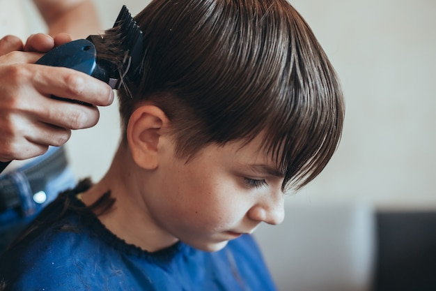 Hairdresser does a haircut with clipper for a boy