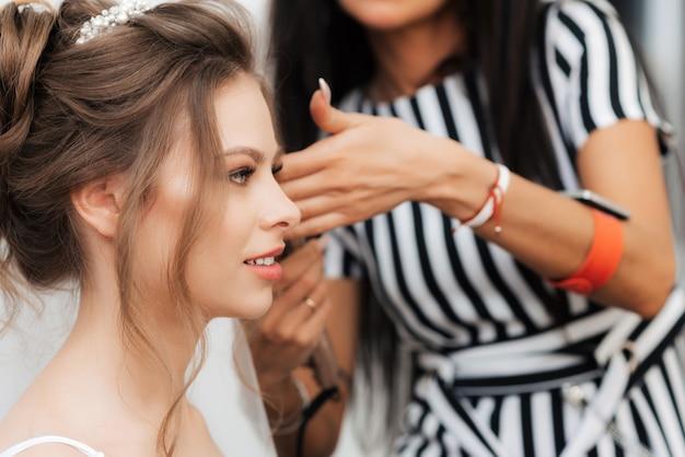 美容師は美しい女の子の花嫁のスタイリングを行います