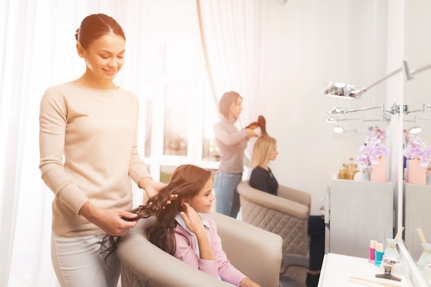 Hairdresser doing hair styling to a small dark-haired girl.