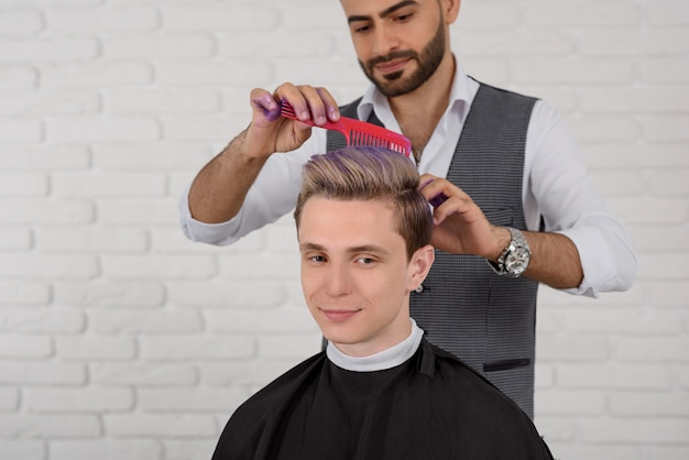 Hairdresser doing hair violet colored toning for young boy.