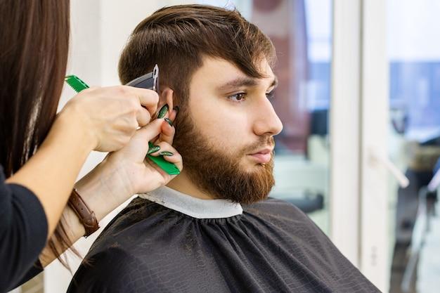 Парикмахер делает стрижку для клиента мужского пола, человек с бородой, используя профессиональные инструменты парикмахера, оборудование на рабочем месте парикмахера, на рабочем месте. парикмахерские услуги. парикмахерская стрижка, стрижка бороды.