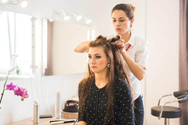 美容院で女性のための散髪をしている美容師。ファッションと美容の概念。ポジティブな感情。