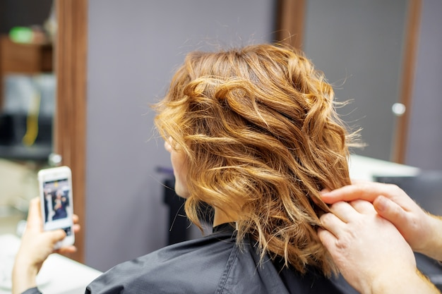 Hairdresser doing hairstyle for young woman with red curly hair and with smartphone in her hands in beauty salon