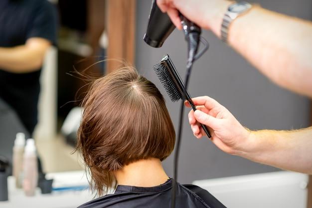 미용사는 미용실에서 젊은 여자의 갈색 머리를 말립니다