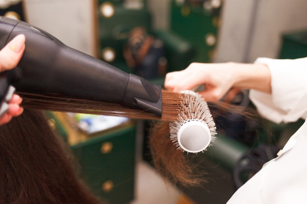 Hairdresser dries hair of a client with hairdryer and comb. woman in beauty salon