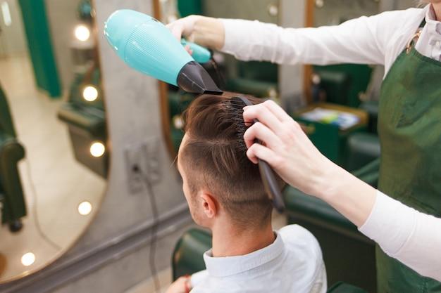 Парикмахер сушит волосы стильного мужчины. молодой красивый парень делает укладку волос в парикмахерской