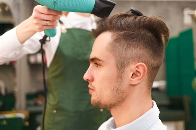 Hairdresser dries hair of stylish man. young handsome guy doing hair styling at a hairdresser
