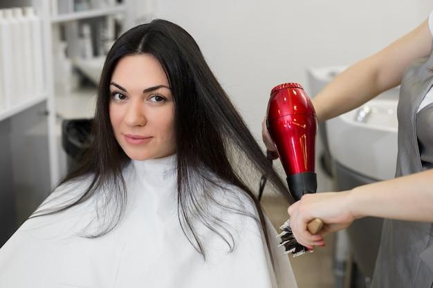 美容師はヘアドライヤーで女の子の濡れた髪を乾燥させ、櫛をとかします