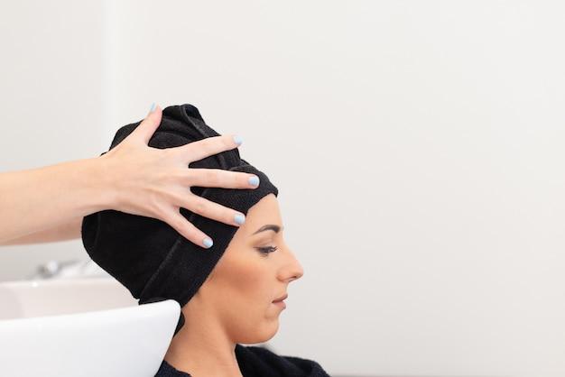 白人のクライアントの髪を流しで洗った後、タオルで乾かす美容師。側面図