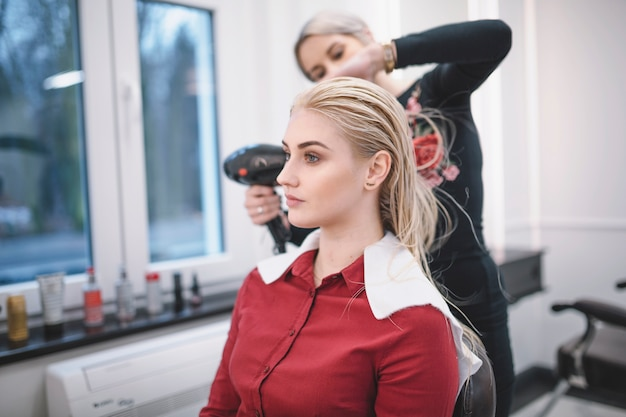 Hairdresser drying customer with hairdryer