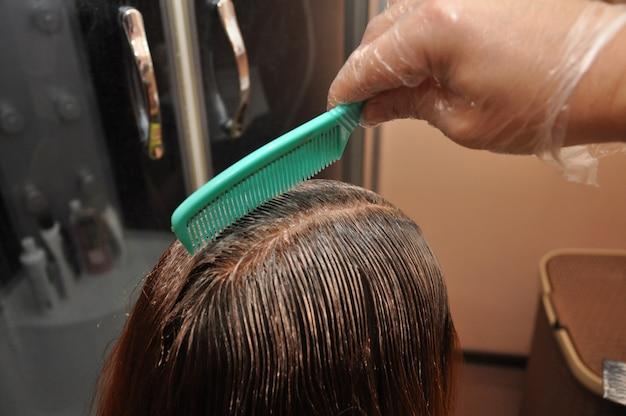 Парикмахер, окрашивающий волосы клиента