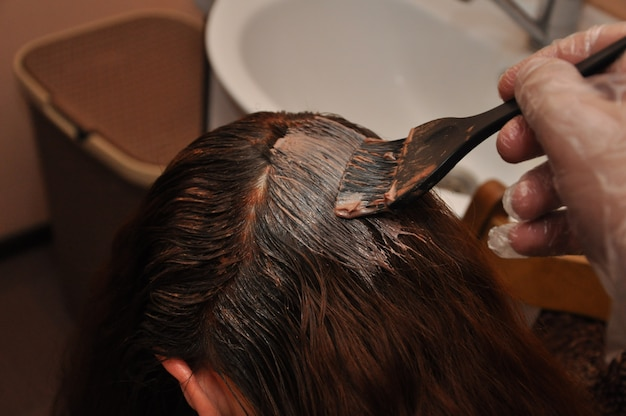 Hairdresser dyeing a client's hair