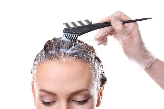 白い背景の上の女性の髪を染める美容師